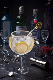 Glas gin-tonic met een paar plakjes citroen erin met de gele drankmixer op de bar, drinkflessen op de achtergrond wazig