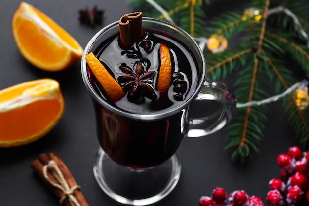 Glas glühwein met kaneel, anijs en sinaasappelen op een feestelijke kerst achtergrond.