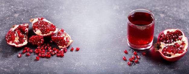 Glas granaatappelsap met vers fruit op donker