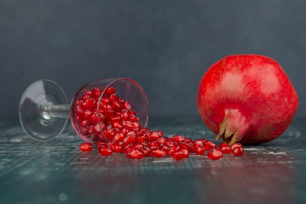 Glas granaatappelzaden en granaatappel op marmeren oppervlak