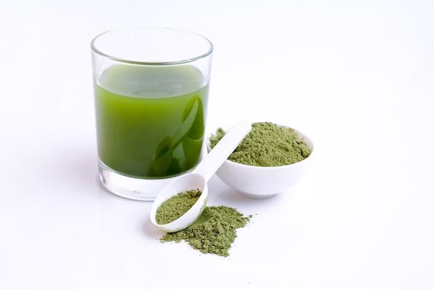 Glas groen groentesap en poeder van groenten op lepel op wit oppervlak