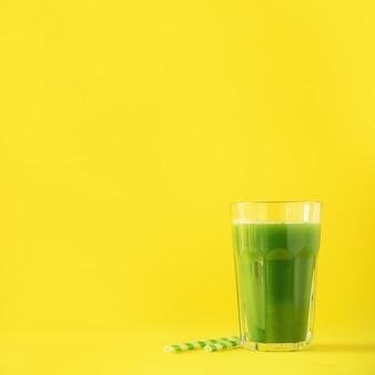 Glas groene selderiesmoothie op gele achtergrond