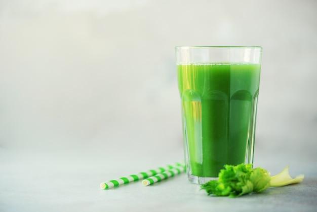 Glas groene selderiesmoothie op grijze concrete achtergrond