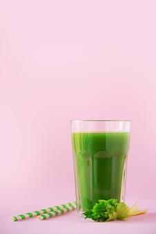 Glas groene selderiesmoothie op roze achtergrond