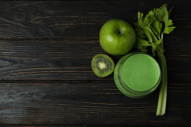 Glas groene smoothie en ingrediënten op houten lijst