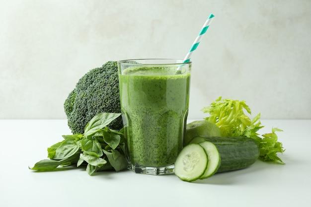 Glas groene smoothie en ingrediënten op witte lijst
