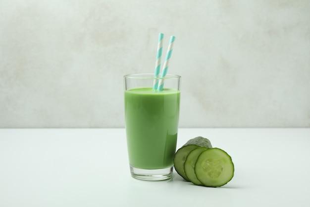 Glas groene smoothie en komkommer op witte lijst