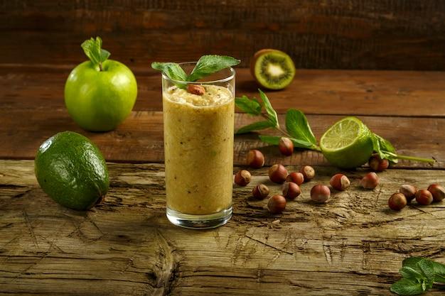 Glas groene smoothie op een houten tafel in de buurt van ingrediënten