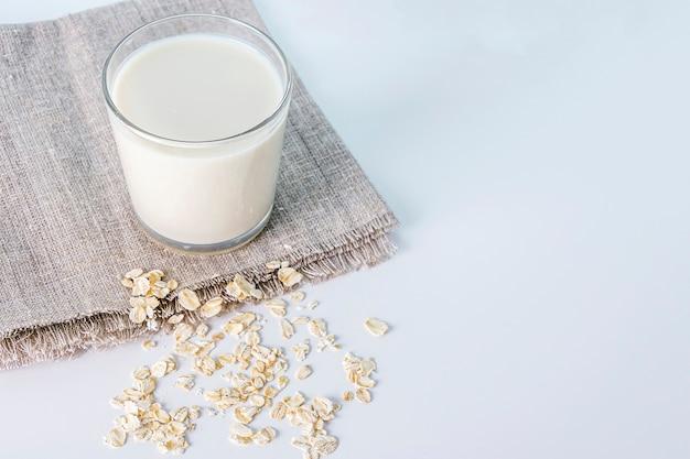 Glas haver plantaardige melk en verspreide havervlokken op tafel