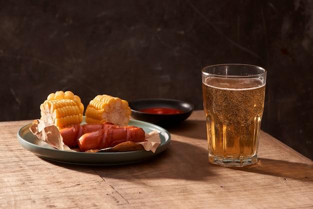 Glas heerlijk bier met gegrilde worstjes op houten tafel