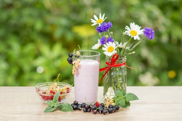 Glas heerlijke bessen yoghurt met verse rode, zwarte en witte aalbessen in een kom en blaadjes munt, kamille en korenbloemen in vaas op een houten tafel met groene wazig natuurlijke achtergrond.