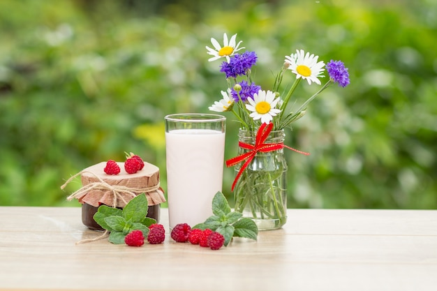Glas heerlijke frambozenyoghurt met verse frambozen, zelfgemaakte aardbeienjam in een pot en blaadjes munt, kamille en korenbloemen in vaas met groene wazige natuurlijke achtergrond.