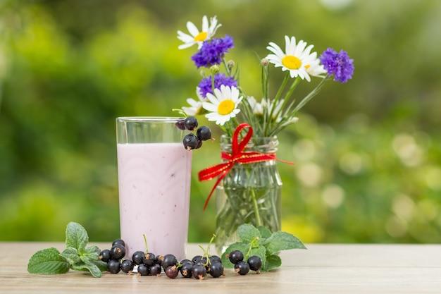 Glas heerlijke krentenyoghurt met verse bessen van aalbes en blaadjes munt, kamille en korenbloemen in vaas op een houten tafel met groene onscherpe natuurlijke achtergrond. selectieve focus close-up