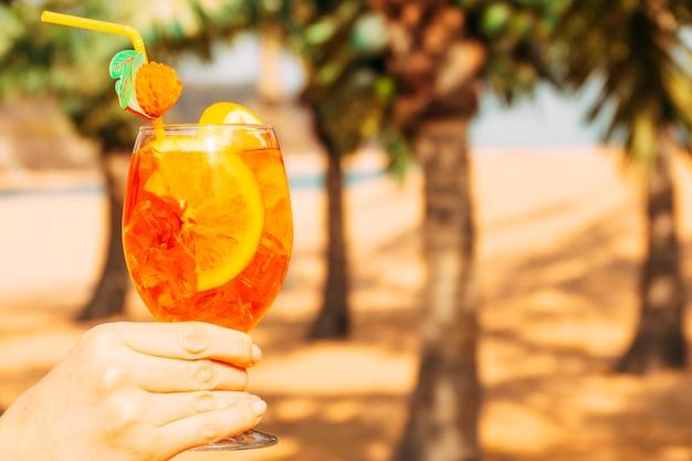 Glas helder oranje drankje in de hand