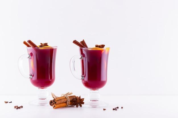 Glas hete glühwein met kruiden op witte achtergrond