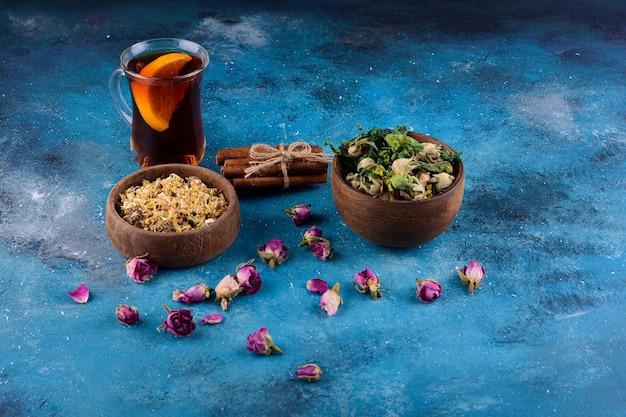 Glas hete thee met gedroogde bloemen op blauwe tafel.