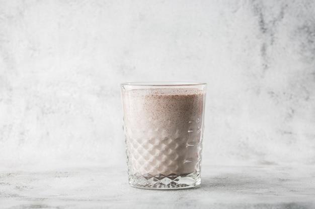 Glas ijscacao of chocolademelk die op heldere marmeren achtergrond wordt geïsoleerd. bovenaanzicht, kopieer ruimte. reclame voor café-menu. coffeeshop menu. horizontale foto.
