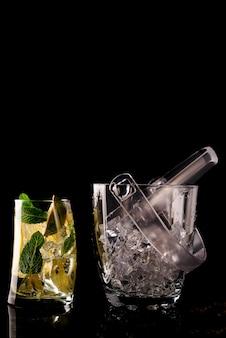 Glas ijsemmer en mohito cocktail in glas geïsoleerd op zwart