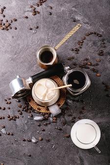 Glas ijskoffie met ijsblokjes geserveerd met room en koffiebonen over donkere ondergrond. bovenaanzicht, plat gelegd. kopieer ruimte