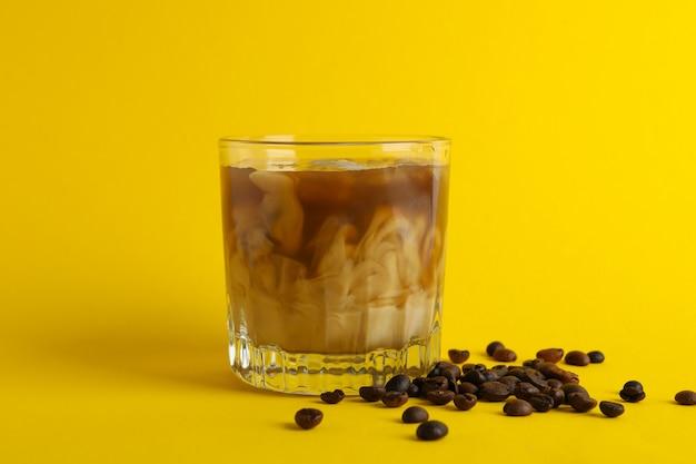Glas ijskoffie op gele achtergrond. vers drankje