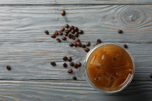 Glas ijskoffie op houten achtergrond. koffie zaden