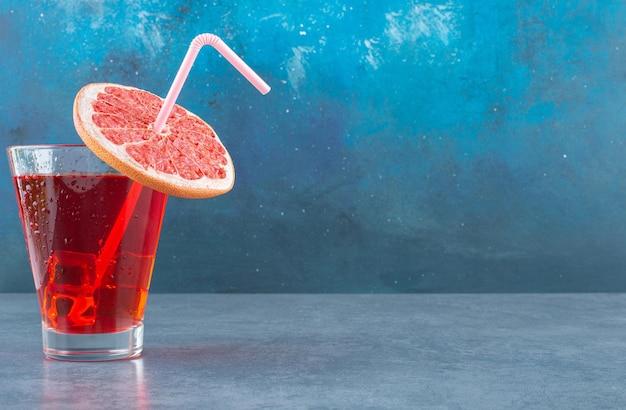 Glas ijskoud sap met een rietje pijp en een schijfje grapefruit op blauw