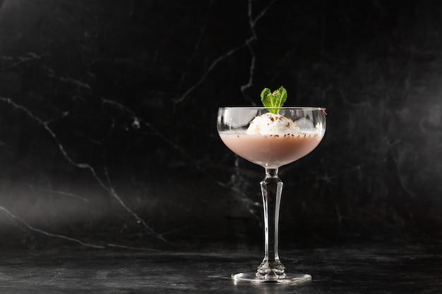 Glas ijskoude baileys-cocktail geserveerd in een coupéglas versierd met muntblad geplaatst
