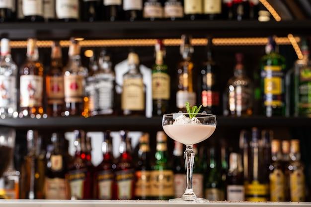 Glas ijskoude baileys-cocktail geserveerd in een glas versierd met muntblad op een bar