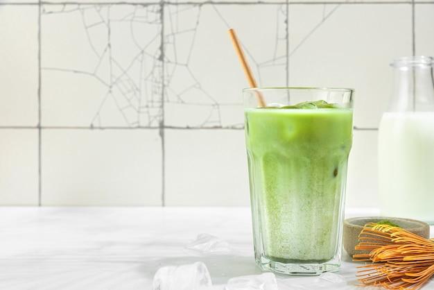 Glas ijskoude groene matcha latte met een rietje en een fles melk op een wit tegeloppervlak met harde schaduwen