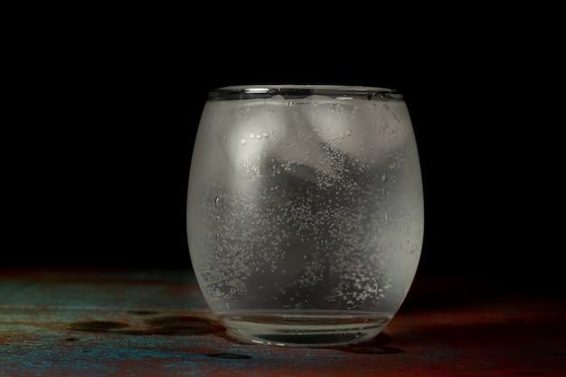Glas ijswater gevuld met koud koolzuurhoudend water op een donkere achtergrond en een rustieke ondergrond.