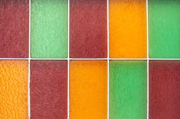 Glas in lood raam. gekleurd vierkant glas in de kaders. rood, groen en geel glas. achtergrond of textuur