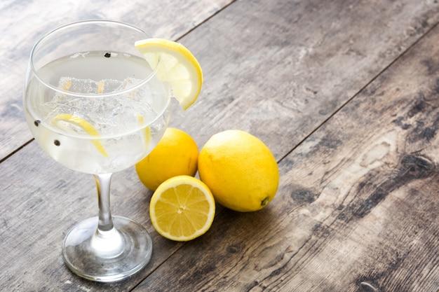 Glas jenevertonicum met citroen op houten lijst