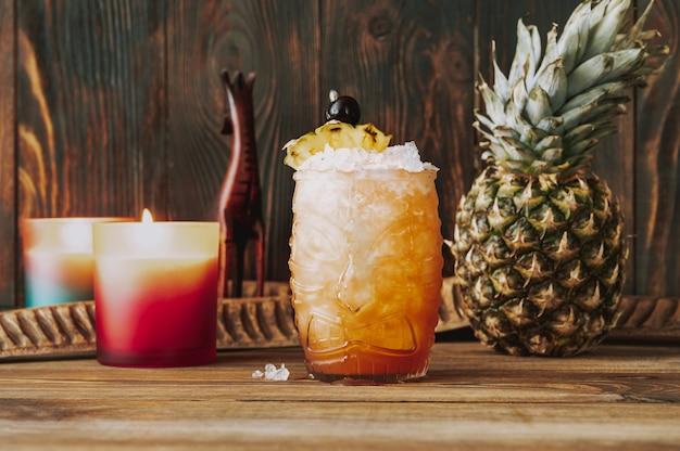 Glas jungle bird-cocktail gegarneerd met een schijfje ananas