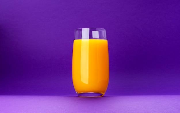 Glas jus d'orange dat op violette achtergrond met exemplaarruimte wordt geïsoleerd