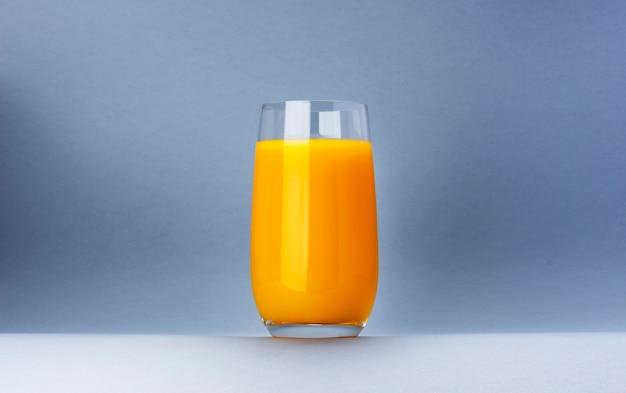 Glas jus d'orange dat op witte achtergrond met exemplaarruimte wordt geïsoleerd