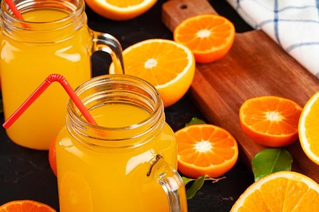 Glas jus d'orange en gesneden sinaasappelen op tafel