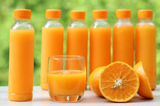 Glas jus d'orange en sinaasappelen op natuurlijke groene ruimte