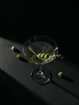 Glas klassieke droge martini cocktail met olijven op donkere stenen tafel tegen een zwart oppervlak.