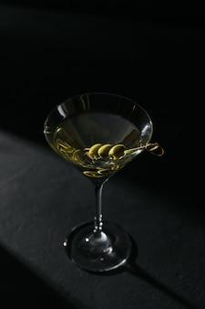 Glas klassieke droge martini cocktail met olijven op donkere stenen tafel tegen een zwarte achtergrond.