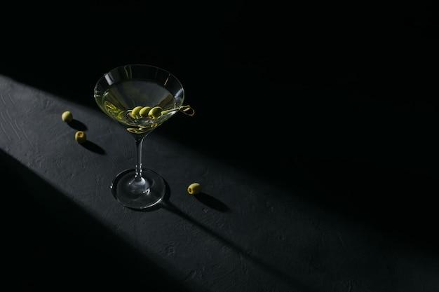 Glas klassieke droge martini-cocktail met olijven op donkere stenen tafel tegen een zwarte achtergrond