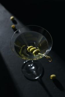 Glas klassieke droge martini cocktail met olijven op donkere stenen tafel tegen een zwarte.