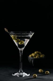 Glas klassieke droge martini cocktail met olijven op donkere stenen tafel tegen zwart