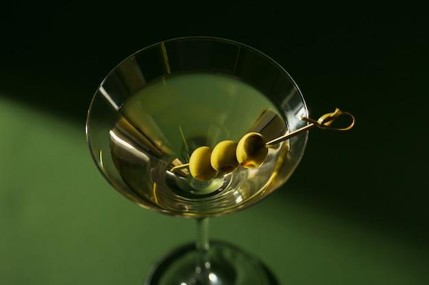 Glas klassieke droge martini-cocktail met olijven op donkergroen