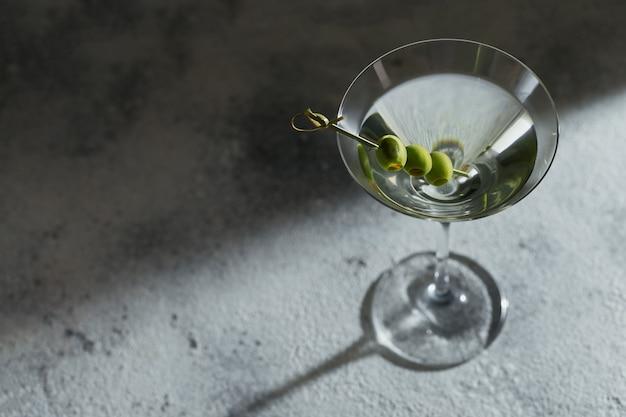 Glas klassieke droge martini-cocktail met olijven op grijze steenachtergrond