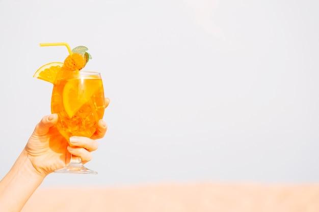 Glas koelen oranje drankje in de hand