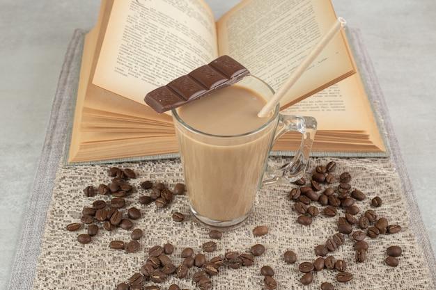 Glas koffie met chocolade, boek en koffiebonen op jute