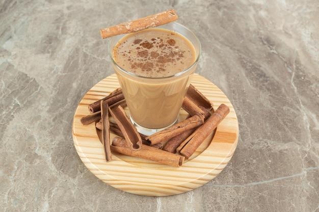 Glas koffie met kaneel op houten bord