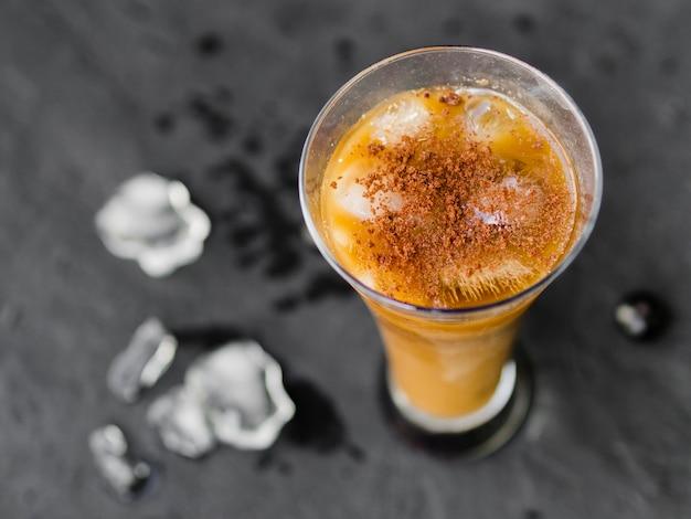 Glas koffiecocktail met ijsblokjes en poeder