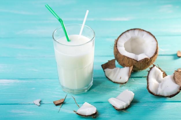 Glas kokosmelk op blauwe houten lijst. selectieve aandacht