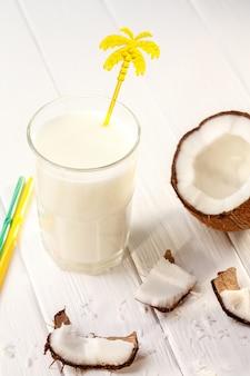Glas kokosmelk op witte houten lijst, bananen. tropisch. selectieve aandacht